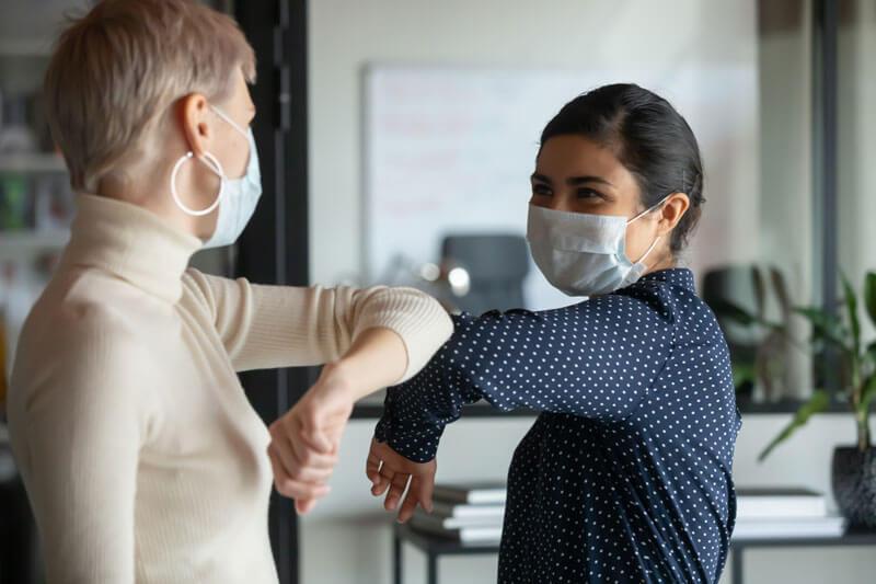 2 Frauen mit Mundschutz begrüßen sich