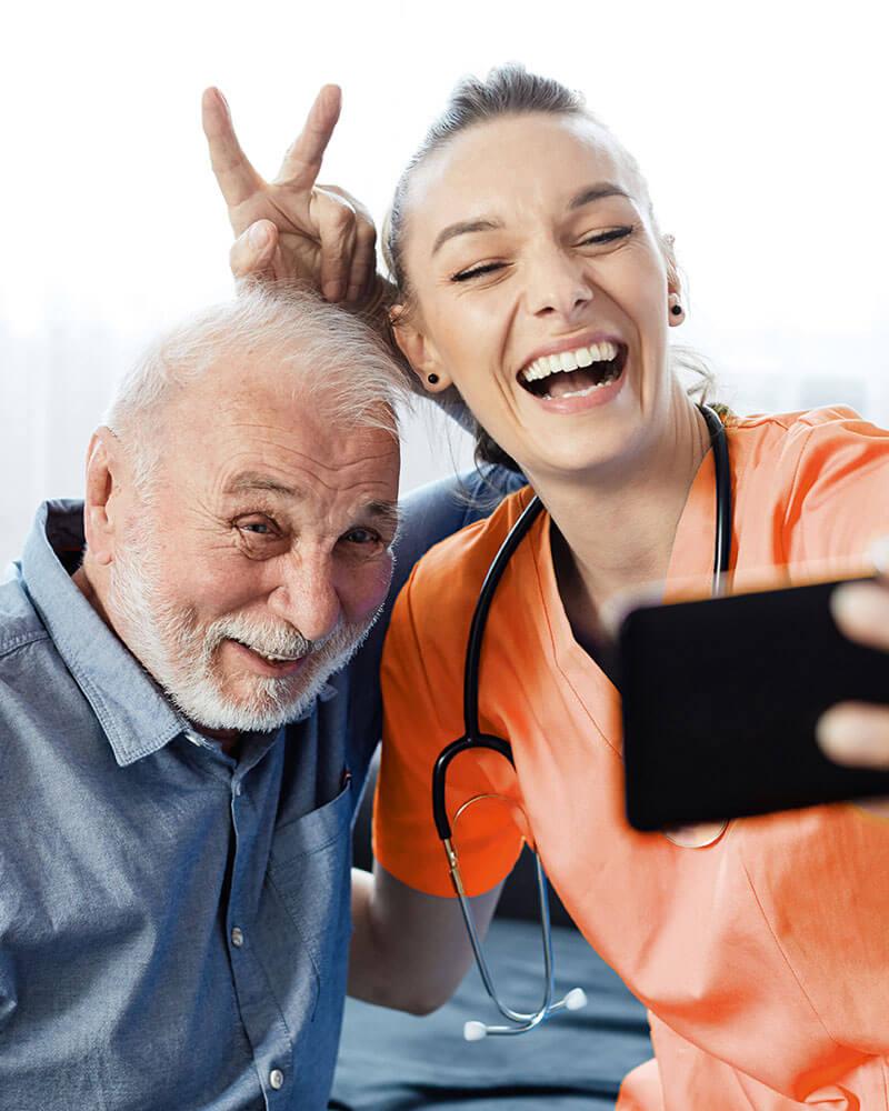 Pflegerin und Senior haben Spaß beim Selfie machen
