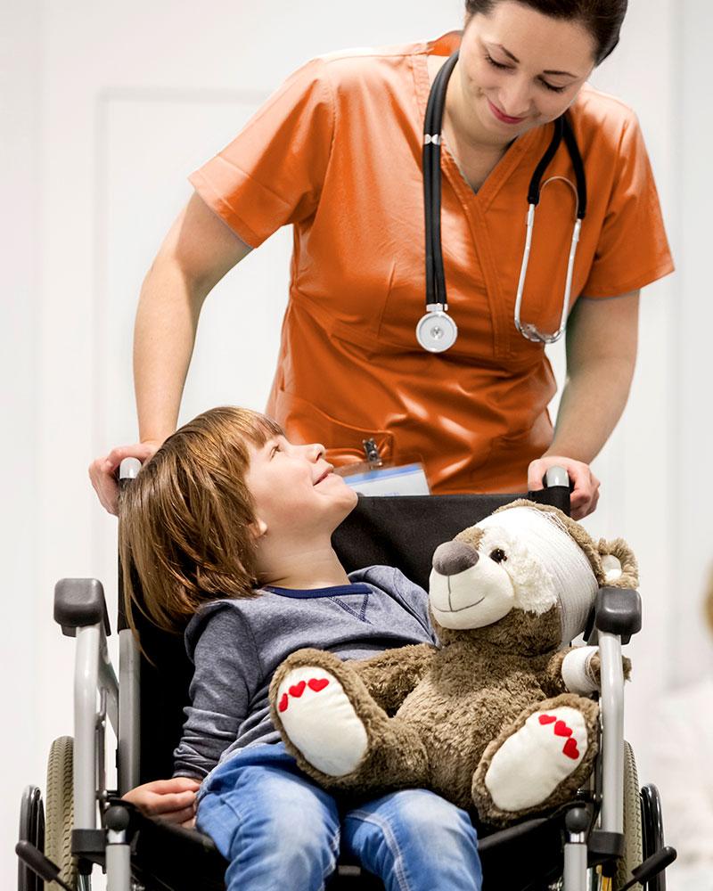 Pflegerin schiebt Junge im Rollstuhl